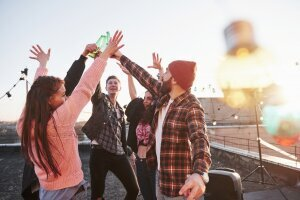decorative_festive_light_bulbs_holidays_rooftop_cheerful_group_friends_raised_their_hands_up_with_alcohol